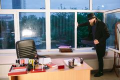 Concept. The thief comes into the office through the window. Thief in the office.  stock photo