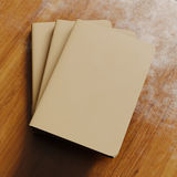 Concept of three blank notebook with brown craft paper cover on wooden desk.Closeup empty horizontal mockup.Top view. 3d Stock Photo