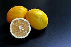 Concept of a three lemons, two whole and one half on black background. royalty free stock photography