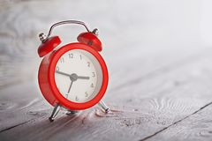 Concept of time, red clock on light wooden background Stock Images