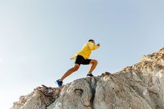 Concept to overcome difficulties. Man in sports clothes climbing steep mountain stock photography