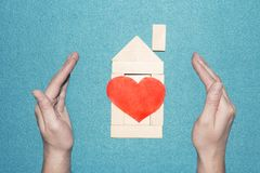 Concept is to protect and love the house. Protection of the home and family. Insurance of real estate. Wooden toy house of cubes with red heart inside and Stock Photography