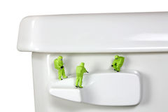 Concept: Toilet germs. Concept image of a miniature HAZMAT (Hazardous Materials) team inspecting the germs and bacteria on a toilet handle. White background Stock Photo
