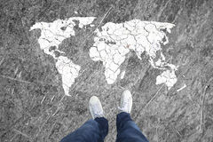 Concept top view of a man and world map. Top view of a man legs and soil textured and cracked world map on the grunge floor. Personal perspective used stock photography