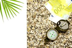 The concept of tourism. Compass with Euro lies on the sand, to the left is a place for text isolate stock image