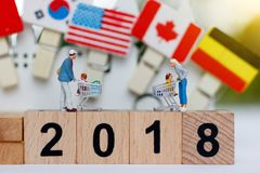 Miniature people family with shopping cart on wood block with number 2018. Concept of tourism, shopping or business. Miniature people family with shopping cart Stock Photo