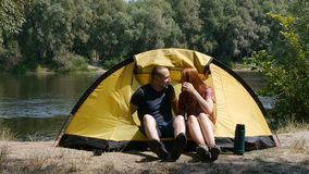 Concept of tourism and travel. Young happy couple sitting in tent watching the view. The beautiful nature surrounds. Young people. Drinking a tea stock video