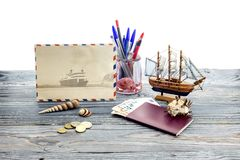 The concept of tourism by water transport. The concept of tourism and travel by water transport. Passport, money, coins, seashells, and a toy ship on a wooden Royalty Free Stock Images