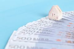 The concept of a toy house on a background of banknotes of 500 euros royalty free stock image