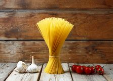 A bunch of Italian spaghetti, garlic, and cherry tomatoes on a wooden background. Concept: traditional Italian cuisine. royalty free stock image