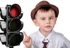 The concept of traffic rules. A little boy is pointing at a traffic light. The concept of traffic rules royalty free stock image
