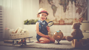 Concept travel. child girl at home dreaming of travel and touris Royalty Free Stock Image