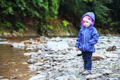 The concept of travel and childhood. Little girl stands near the river.  The concept of travel and childhood Royalty Free Stock Photos