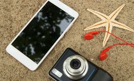 The concept of travel planning and vacation on the sea sand. Top view smartphone, camera, starfish, headphones.  Stock Photo