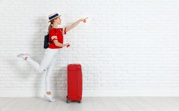 Concept travel and tourism. girl with red suitcase near white em Stock Photography