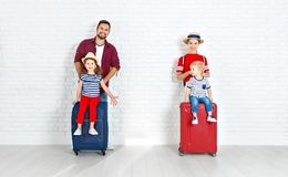 Concept travel and tourism. happy family with suitcases near   w. Concept travel and tourism. happy family with suitcases near empty wall Royalty Free Stock Image