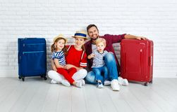 Concept travel and tourism. happy family with suitcases near   w. Concept travel and tourism. happy family with suitcases near empty wall Royalty Free Stock Photos