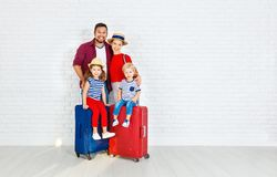 Concept travel and tourism. happy family with suitcases near   w. Concept travel and tourism. happy family with suitcases near empty wall Stock Photography