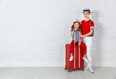 Concept travel and tourism. mother and child daughter with suitc. Ase near empty wall Stock Images