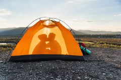The concept of travel, tourism and relationships. Silhouette of a young man and his girlfriend who kisses each other in. Silhouette of a young man and his royalty free stock photography