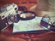 Concept of travel traveler travelling. Sunglass camera map and hat on brown leather background.Copy Space vintage tone. Toned Image Stock Image