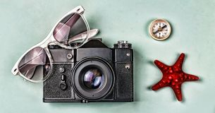The concept: travel, vacation, active leisure, sea voyages. Ancient camera, sunglasses, old compass and starfish on a blue backgro Stock Photography