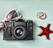 The concept: travel, vacation, active leisure, sea voyages. Ancient camera, sunglasses, old compass and starfish on a blue backgro Royalty Free Stock Image