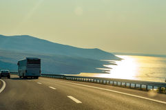 Concept of traveling to the sea, tourism, bus, road and the seas. Ide, with some hills in the background at the sunset, light reflecting on the water with royalty free stock image
