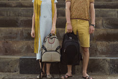 Concept traveling together, honeymoon. Stylish couple in love with backpacks standing on footstep Stock Photography