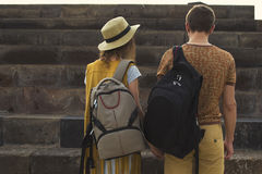 Concept traveling together, honeymoon, wanderlust. Stylish couple in love with backpacks on shoulders. Back view. Royalty Free Stock Photography