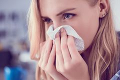 Girl blows her nose into a tissue. Portrait of a woman with tissue in hands looking away. Concept of treatment for. Concept of treatment for allergies or the Royalty Free Stock Photography