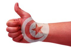 The concept of Tunisia-the hand gives a thumbs up with the flag of Tunisia. Hand and flag of Tunisia royalty free stock photography