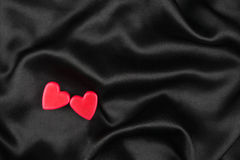 The concept of two lovers hearts lying on the black satin Stock Photos