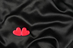 The concept of two lovers hearts lying on the black satin Royalty Free Stock Photography