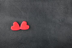 The concept of two lovers hearts lying on the natural leather Stock Image