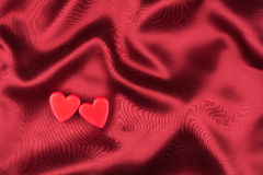 The concept of two lovers hearts lying on the red satin Stock Photos