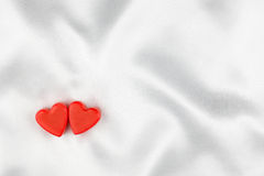 The concept of two lovers hearts lying on the white satin Royalty Free Stock Image