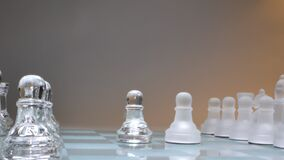 Concept two pawns standing opposite, two powers, glass chess
