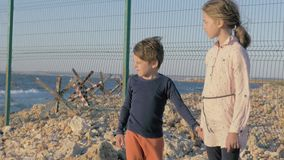 Two poor refugee children standing by the sea in war conflict zone. boy and girl waiting to be rescued stock video footage