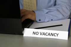 No vacancy sign in office, businessman in blue shirt and tie sitting at desk with laptop royalty free stock photo