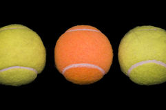 Concept: Unique. An Orange Tennis Ball Surrounded by Two Green Tennis Balls stock photos