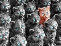 Concept of unique and outstanding. Red cat figure stands out amo royalty free stock photo