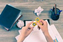 Concept of using fidget spinner at work while having a break. Hands holding fidget spinner over desktop with books, pens, clipboar stock images