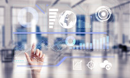 Concept of using modern technologies for business globalization. Hand of woman working with media interface on screen and office interior at background Stock Images