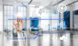 Concept of using modern technologies for business globalization and networking. Hand of businesswoman working with media interface on screen and office interior Royalty Free Stock Photography