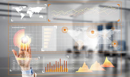 Concept of using modern technologies for business globalization and networking. Hand of businesswoman working with media interface on screen and office interior Stock Photography