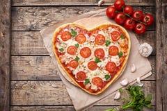 Concept végétarien d'amour de margherita en forme de coeur de pizza avec la composition en mozzarella, en tomates, en persil et e Photo stock