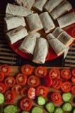 Concept végétarien sain de petit déjeuner : tacos roulé de fromage de plat rouge avec les tomates et les concombres coupés en tra Photographie stock