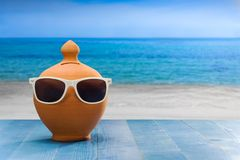 Concept Vacations, money box with sunglasses on wooden plank, beach background. Vacation, ceramic Money box on blue wooden floor stock images