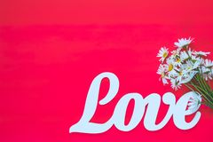 Concept for Valentine day or Wedding, Birthday, Mother day. White letters forming word LOVE written with chamomile flowers on pink background. Beautiful concept stock image